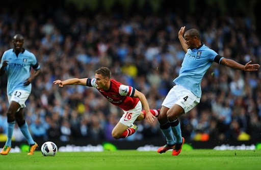 Arsenal midfielder Aaron Ramsey is tackled by Manchester City captain Vincent Kompany