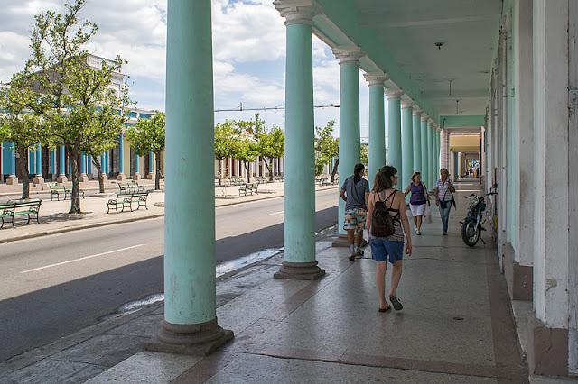 Passants sous une colonnade du Paseo del Prado