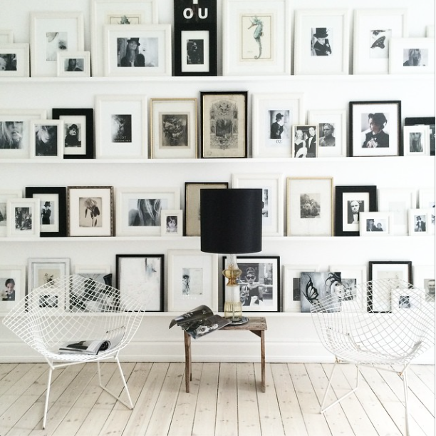 Gallery wall with black and white framed photographs on wide white shelves. #blackandwhite #gallerywall