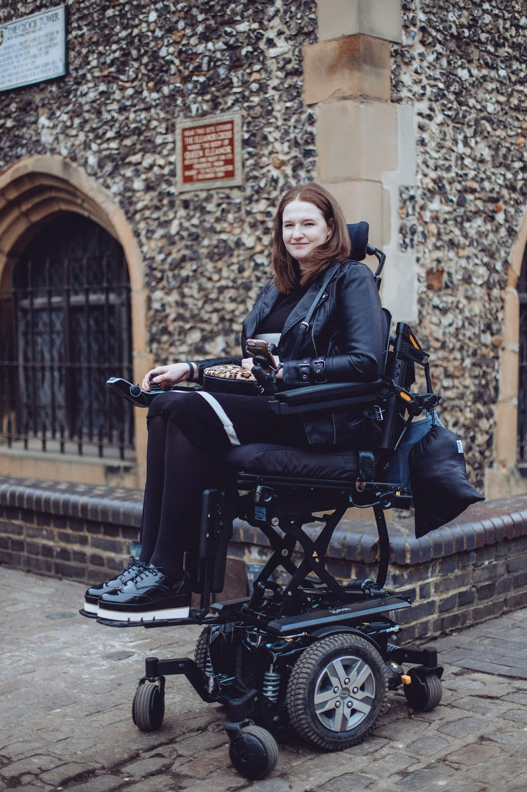 Shona is sitting in her powerchair smiling, her powerchair is raised up 10 inches using the elevate function. Shona is wearing a black dress, black and white flatform shoes, a leather look jacket and a loepard print bag. She is smiling.