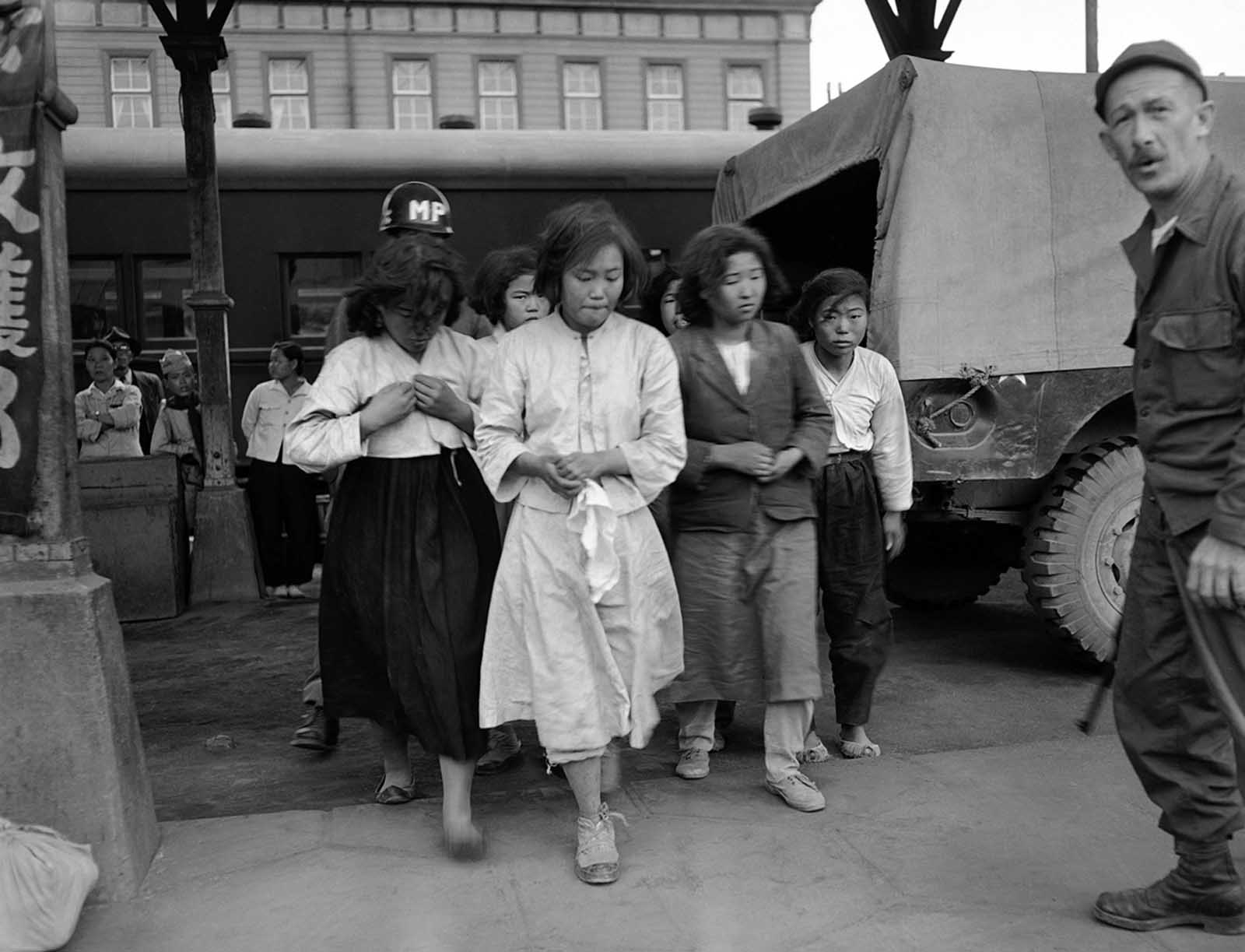 Captured by American forces in the Taegu area of South Korea on October 8, 1950, these North Korean girls are marched to a train which will take them to a prisoner of war camp at Pusan.