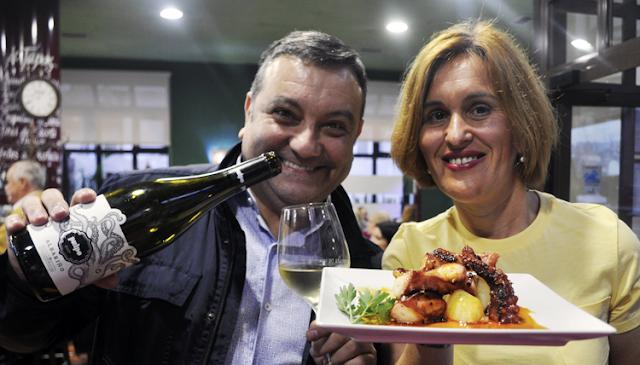nacho sostiene la botella de Albariño y sonrie a la camara, Noelia con camiseta amarilla sonríe y sostiene un plato de pulpo en La terraza de Viesques