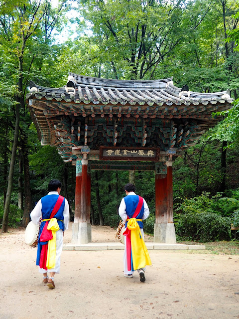 Musicians in traditional costume, walking through an arch at the Korean Folk Village, Yongin, Gyeonggi-do, South Korea