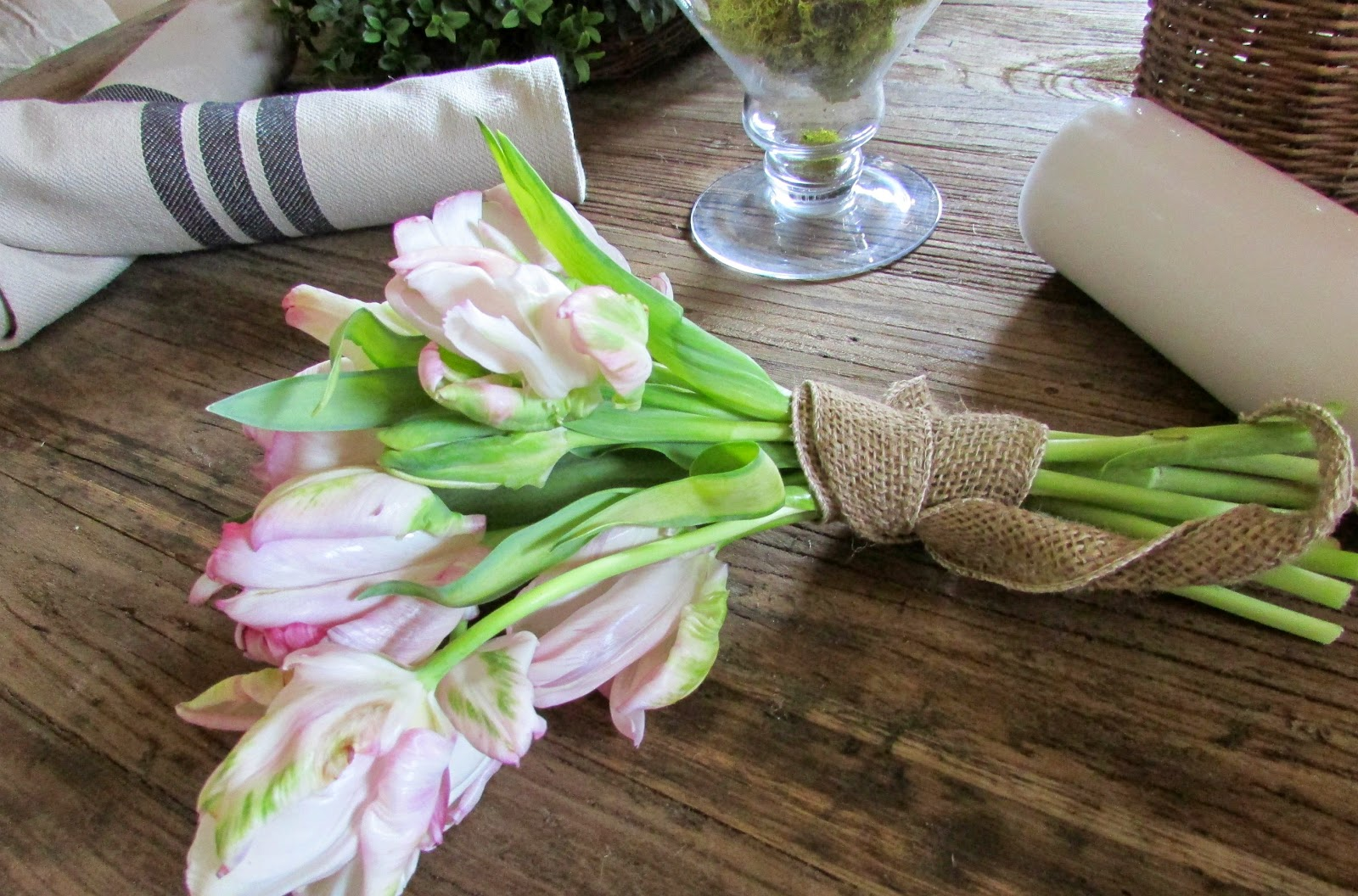 Moss, Tulips and Demi-John Centerpiece on a Rustic Table