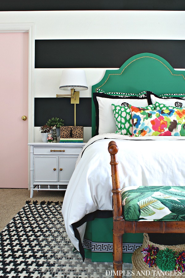 pink door, black and white striped wall, green upholstered headboard, wall sconces, vintage bamboo nightstands, black and white crosses rug, crane and canopy linden duvet, monogrammed pillows, large scale floral pillow