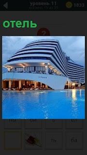 Необычной формы отель расположен около прозрачной воды. На террасе находятся шезлонги для отдыха