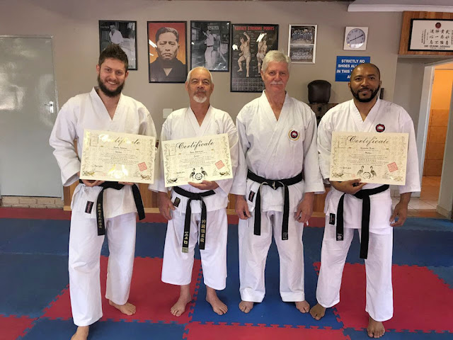 Four karateka receiving certificates