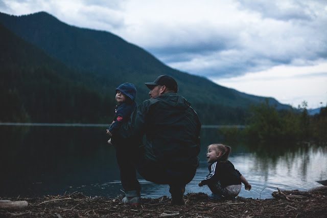 A family sat on the edge of a lake overlooking a mountain.