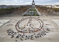 "Environmentalist activists form a human chain representing the peace sign and the spelling out ""100% renewable"", on the side line of the COP21, United Nations Climate Change Conference near the Eiffel Tower in Paris, Sunday, Dec. 6, 2015. (Credit: AP Photomichel Euler) Click to Enlarge."