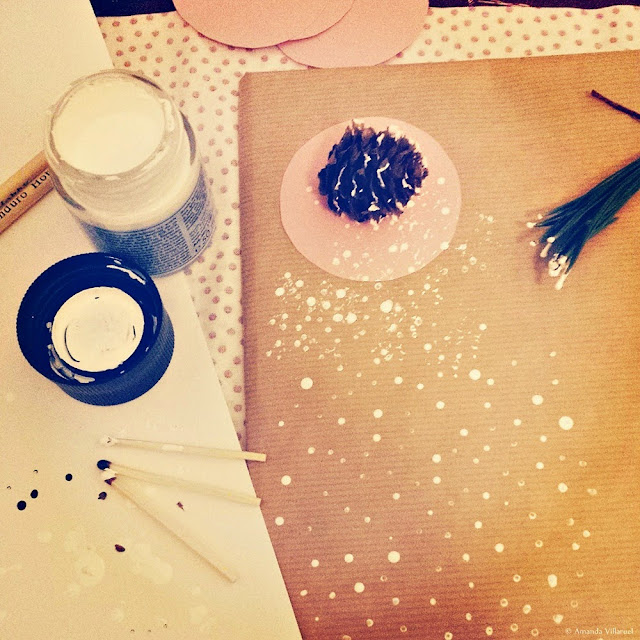 Painting snow crystals on brown wrapping paper using matches