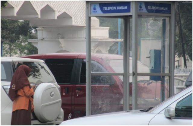 Box telepon umum menggunakan koin yang berada di pelataran Masjid Agung Medan