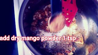 image of adding dry mango powder in stuffing