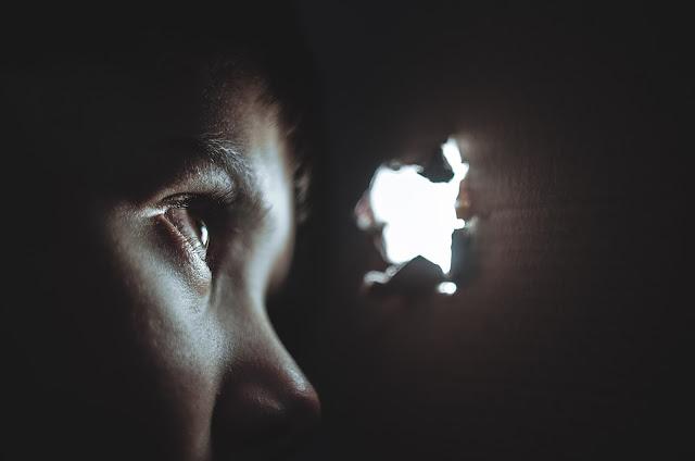 Niño que curiosea por un agujero