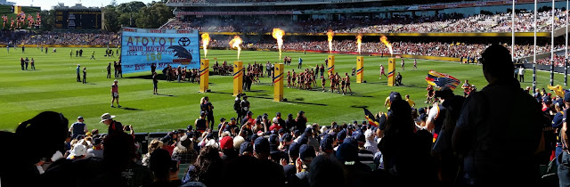 A view of Adelaide Oval from the southern stand.  A guard of honour is formed by yellow flame throwing pots and visiting football teams. The Adelaide Crows team are walking through with the intention of running through the banner, a light blue rectangular shape towards the centre of the oval.  In the background from left to right one can see a large video screen of the action, the original manual scoreboard, the new eastern stand.