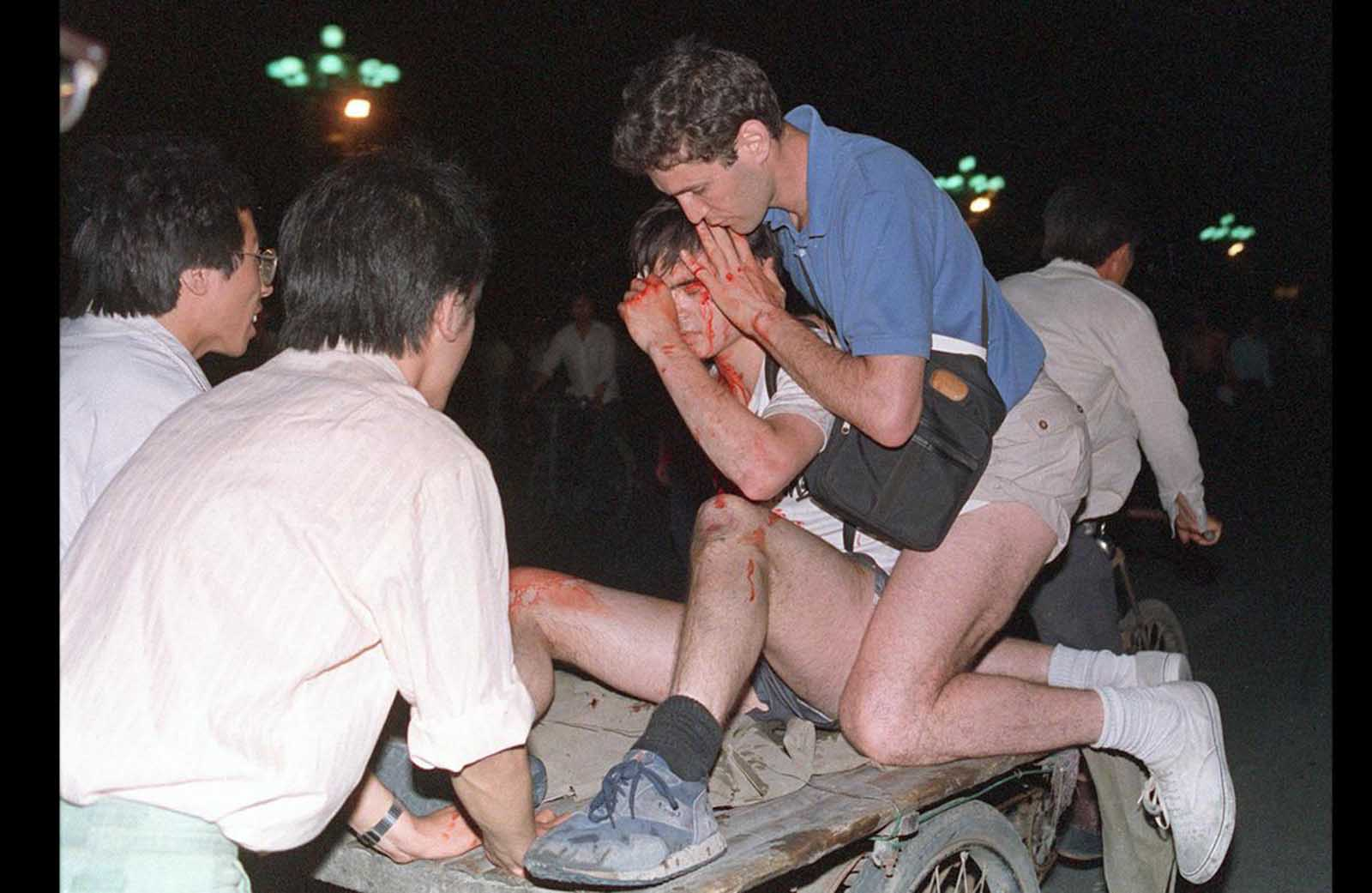 Taken care by others, an unidentified foreign journalist (2nd from right) is carried away from the clash between the army and students near Tiananmen Square, on June 4, 1989.