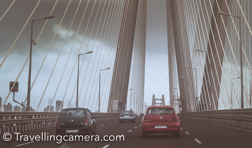 When in Mumbai, we drove around few of the popular places in Mumbai and Travellingcamera visited Sea-link twice in 2 days and loved shooting here. Sea Link connects old Mumbai with new city. This Photo Journey shares more photographs of Sea Link and places from where this beautiful bridge is viewed and clicked.I was staying at JW Marriot near Airport and didn't want to go to other side of Mumbai city  and there is a toll at beginning of Sea Link. So we went till the beginning of Sea Link and took u turn from left after clicking few shots of sea, sea link and high-rise buildings on other side of the sea.I was not happy with what I clicked at this place, so planned to come again but overall all the photographs in my opinion are average. I have seen some of the stunning photographs on web but then realized that I needed to know more about the geography of the place and what makes the best choice to shoot Sea Link.The weather was rainy and it was hazy all around. I clicked some of these plain shots of high-rise buildings on other side of the sea.After taking u turn before the sea link starts, we went to bandstand. After little disappointment about Shahrukh Khan's house at Bandstand, we headed towards Taj LandsEnd and came across these amazing views of Sea link. This certainly is beautiful place to shoot Sea Link and I was imagining how the bridge would look in night when lights on the bridge shine.Next day, plan was to visit Gateway of India and we had to cross the Bridge, so we planned to stop our cab again. Light was a little better, but there was hardly any scope of moving around and trying different things and we were in little hurry.Now we had to cross the bridge, but stopping the cab on bridge was not allowed and our driver strictly conveyed the same to us. So we calmly sat on the back seat and made our cameras to shoot while driving.As we hit the bridge, it started raining heavily and now wiper was also running on the front glass. So we had to manage our clicks i