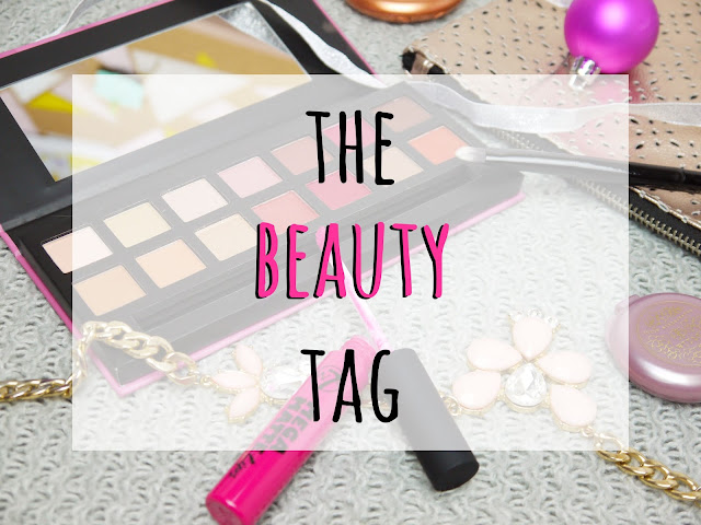 a picture of makeup items like brushes, palette, lipstick, overlaid with black and pink 'the beauty tag' text
