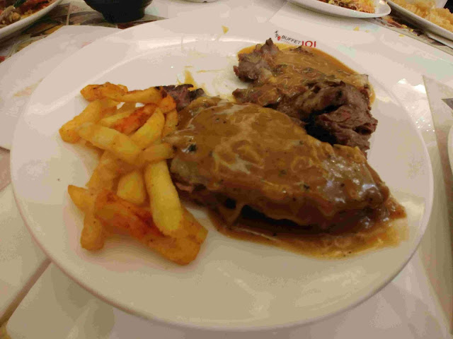 A plate of steak and fries at Buffet 101 Restaurant