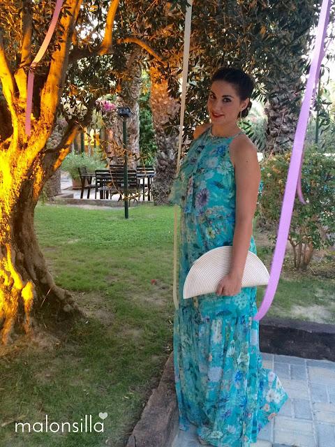 Invitada boda posando en el jardín con vestido largo y bolso