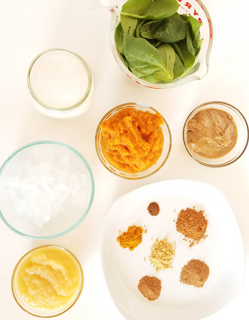 Delicious pumpkin pie smoothie made with pumpkin puree, applesauce, spinach, coconut milk, almond butter, ice, cinnamon, ginger, nutmeg, cloves and turmeric