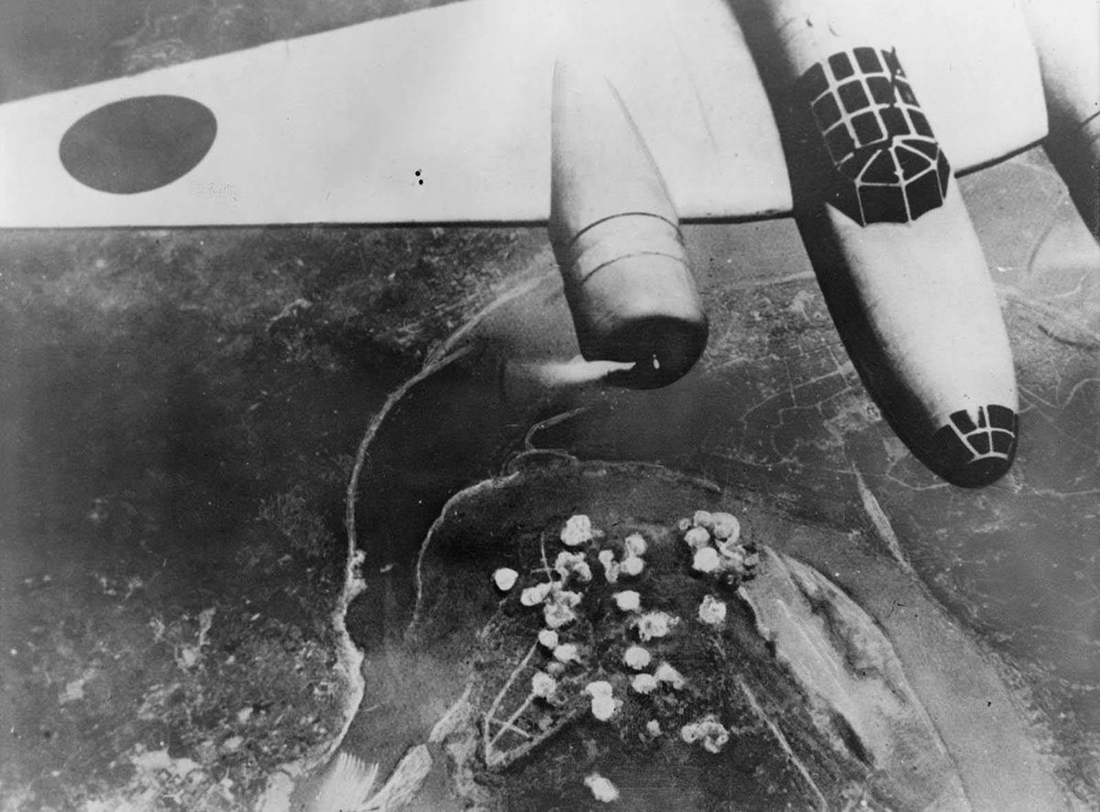 A Japanese bomber in flight on September 14, 1940. Below, smoke rises from a cluster of bombs dropped on Chongqing, China, near a bend of the Yangtze River.