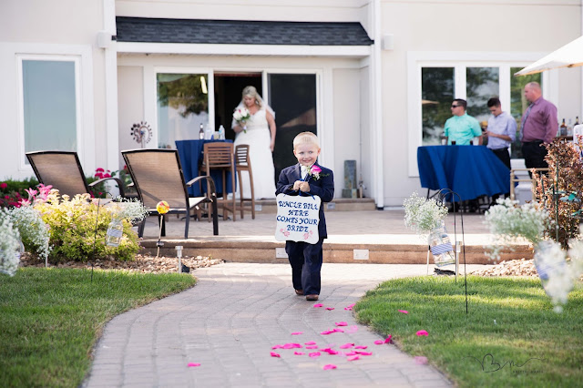ring bearer with sign walking down isle new baltimore waterfront wedding