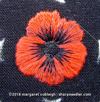 DMC version of embroidered remembrance poppy with black accents towards the centre of the flower