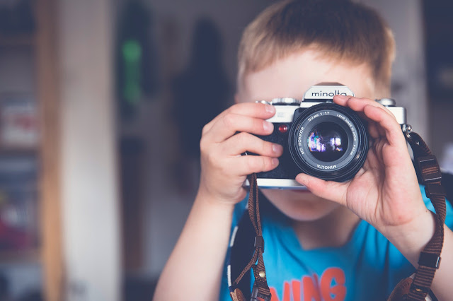 Young boy using a camera, taking a picture