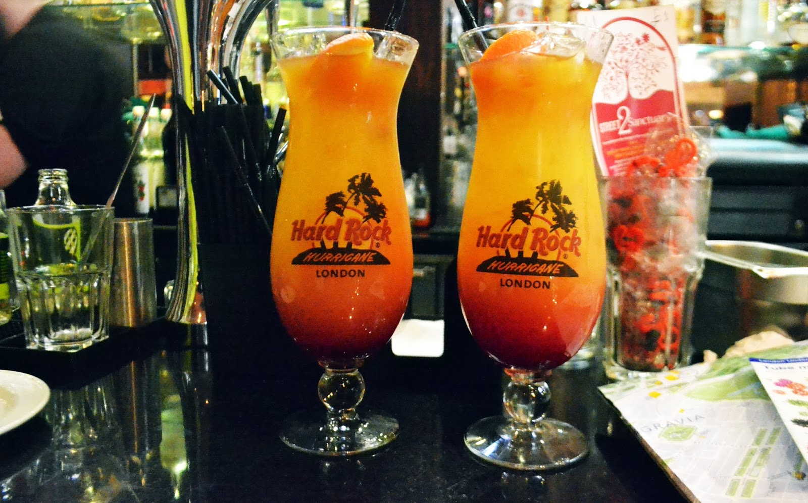 two large cocktails sitting on the bar. the cocktails are a mixture of red and yellow colours