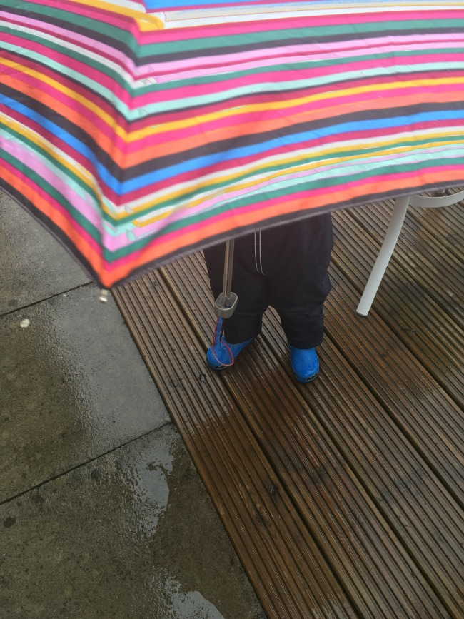 toddler-under-umbrella-just-legs-and-wellies-visible