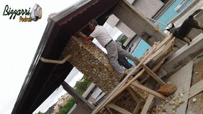 Bizzarri ajudando a fazer o revestimento com pedras do rio, sendo esse revestimento de pedra nos pilares de concreto. Pedra do rio no tamanho de uma laranja.