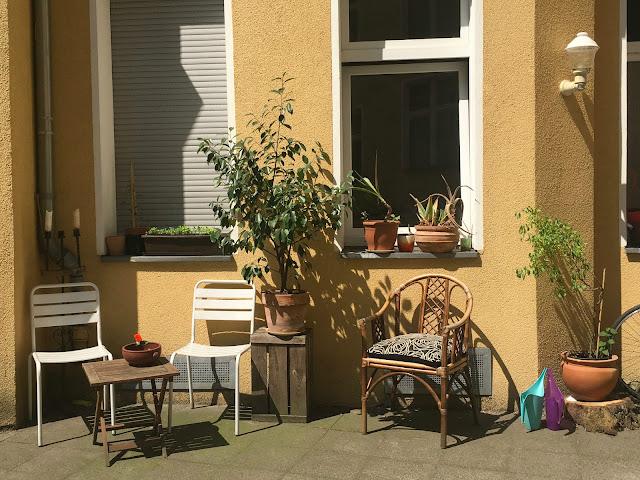 Sonnenbeschienene Wand, Sitzgelegenheiten, Tischchen, Pflanzen