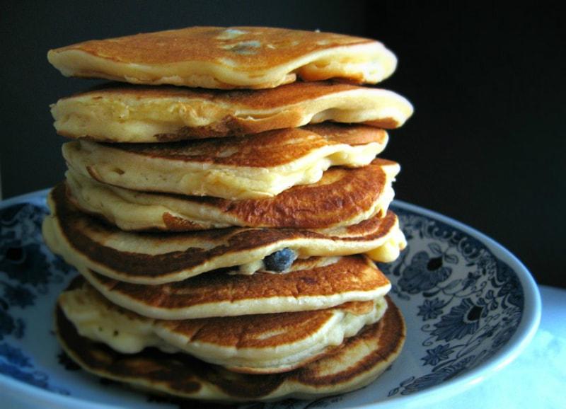 Panquecas de mirtilos e ricotta empilhadas sobre prato azul / Stacked blueberry & ricotta pancakes on a blue plate
