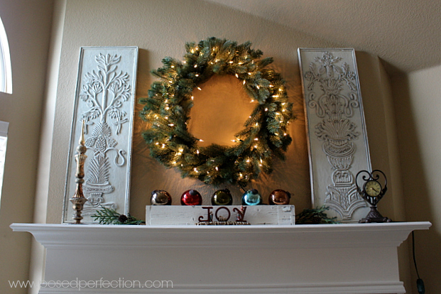 Christmas mantel featuring large pre-lit Tree Classics wreath and painted wooden panels.