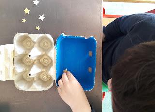 Um aluno a enfeitar o presépio com estrelas feitas em papel dourado