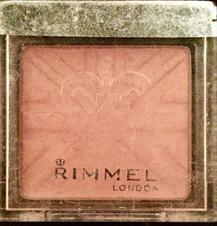 A square pot filled with a bright pink blush with a clear plastic lid with Rimmel on the front of it on a bright background.