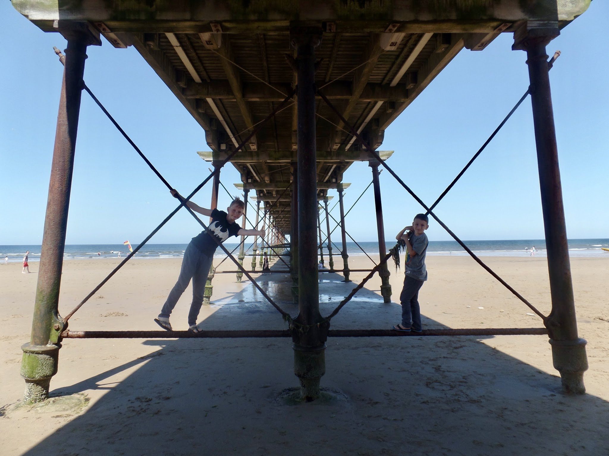 View under the pier with 2 boys climbing on the pier
