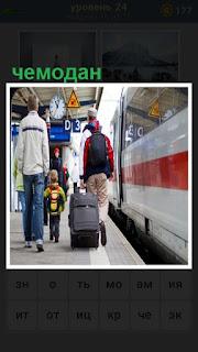 по платформе везут чемодан на колесах рядом с поездом
