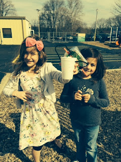 Two young girls holding egg project in a cup