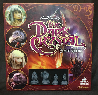 The cover of the game. The title is displayed superimposed over the titular crystal, with the castle of the crystal visible in the background. Along the left side are the four main characters, each in a circular portrait. Along the bottom is a window covered with clear plastic allowing the four miniatures that are the game's playing pieces to be seen.