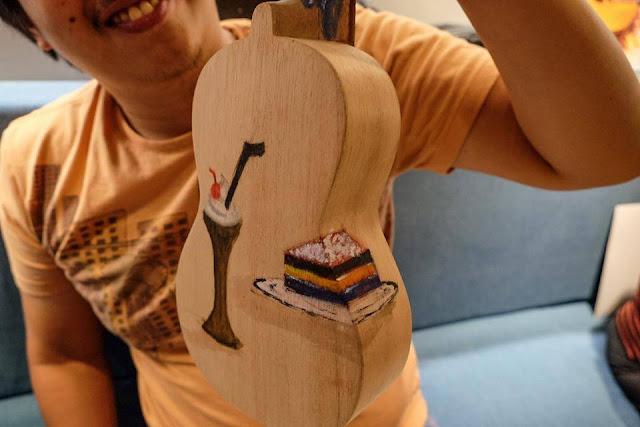 Nat shows off his painted ukulele at UkeHUB Kafe