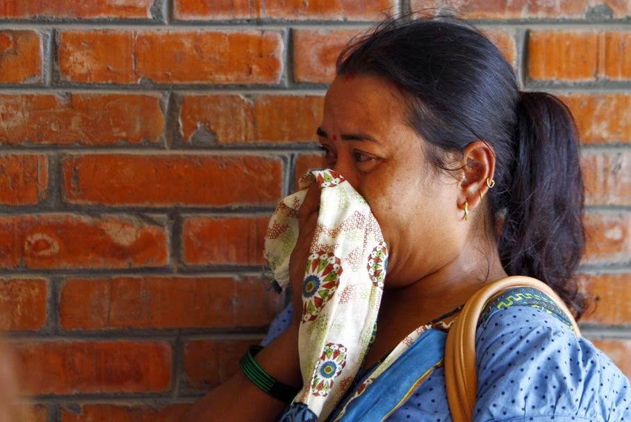 A Nepalese woman cries as a relative injured in a landslide is treated at a hospital in Katmandu, Nepal, Saturday, Aug. 2, 2014. A massive landslide killed at least eight people and blocked a mountain river in northern Nepal on Saturday, causing the water to form a lake that was threatening to burst and sweep several villages, officials said.