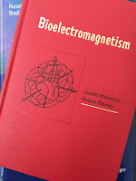 Bioelectromagnetism: Principles and Applications of Bioelectric and Biomagnetic Fields, by Jakko Malmivuo and Robert Plonsey, superimposed on Intermediate Physics for Medicine and Biology.