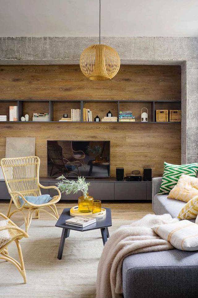 Salón con pared forrada en madera y marco de cemento.