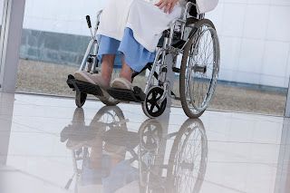 An elderly woman sitting in a wheelchair in a nursing home.