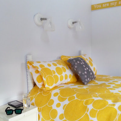 One-twelfth scale modern miniature bed with yellow and white spotty bedding. On the bedside table next to the bed is a Kindle, a glass of water and a pair of sunglasses. Above the bed are two reading lights.