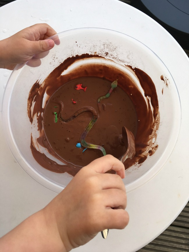 5-minute-games-muddy-creatures-toddler-mixing-plastic-snakes-and-Lidl-stikeez-into-brown-gloop