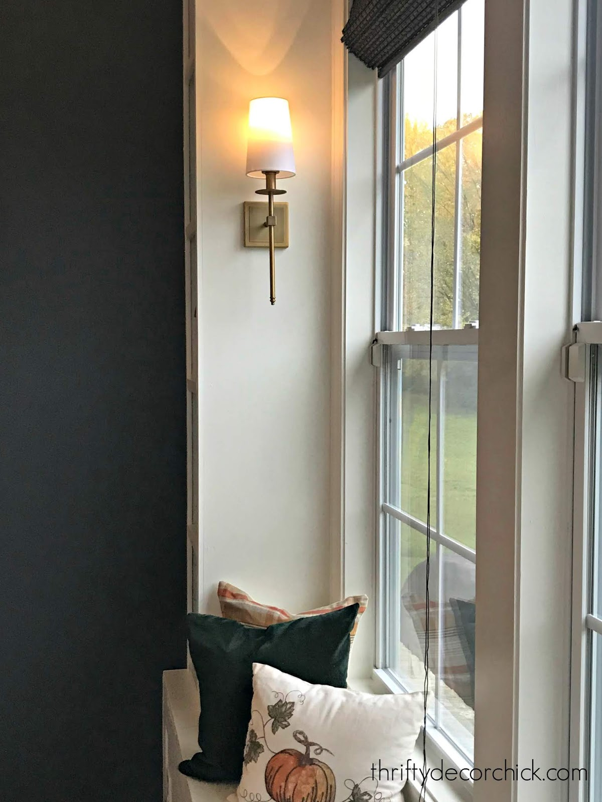 brass sconces around white window seat