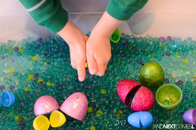 Playing with water beads in an Easter sensory bin from And Next Comes L