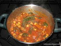 Chickpea and spinach curry cooking, with steam rising out of the pan
